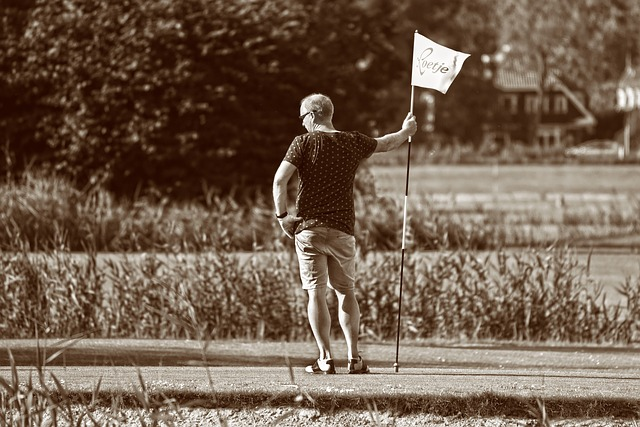 business people playing golf holding flag at the green