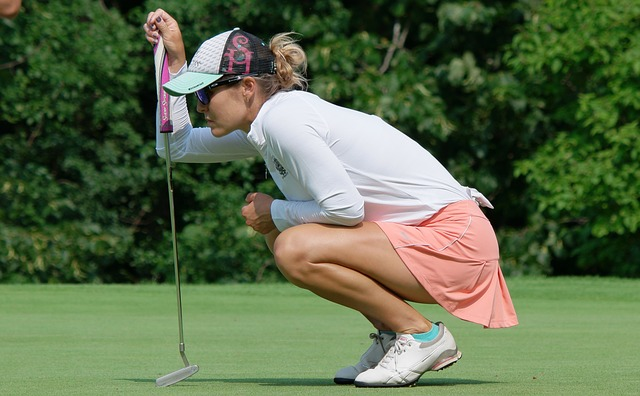 women golfer bending over to look to maneuver green